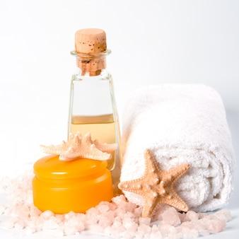 Productos de spa: sal marina, toalla, crema de aceite facial y estrellas.