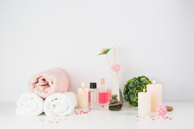 Productos de spa y velas iluminadas sobre tablero blanco.
