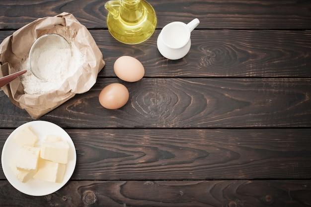 Productos para su preparación de masa sobre mesa de madera oscura.