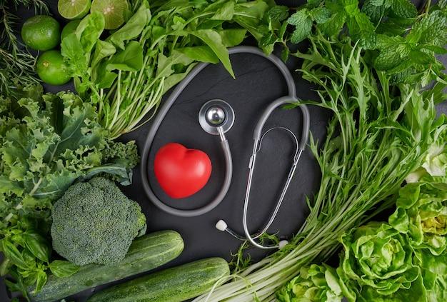 Productos vegetarianos orgánicos verdes con corazón cerca del estetoscopio