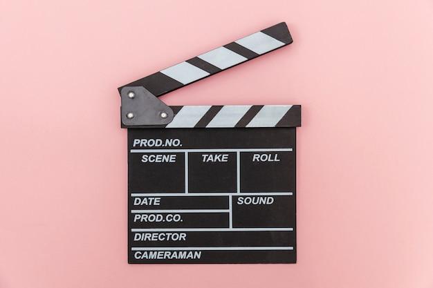 Profesión de cineasta. director clásico película vacía haciendo claqueta o pizarra de película aislada en la pared rosa. concepto de industria de cine de producción de video. vista plana endecha superior copia espacio.