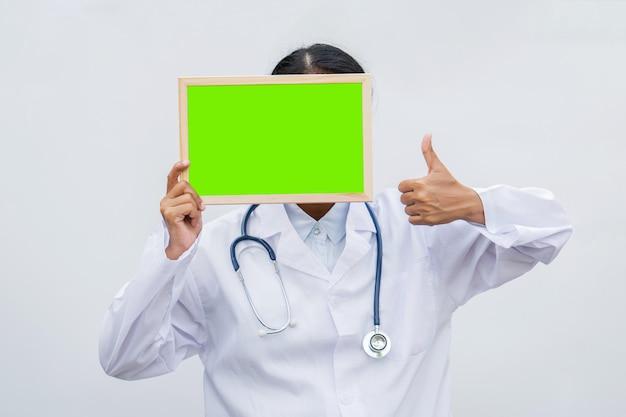 Profesión médico en bata blanca con tablero en blanco y pulgares arriba.