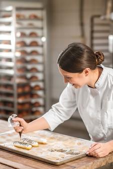 Profesión, pastelero. mujer con experiencia alegre chef de repostería en uniforme blanco decorando con habilidad eclairs dibujo con fondant de chocolate
