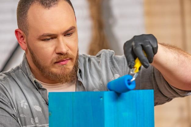 Profesión, personas, carpintería, carpintería y concepto de personas: carpintero que trabaja con tablones de madera y lo cubre con pintura en el taller