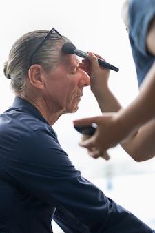 Profesional del artista de maquillaje de la cara haciendo hombre mayor