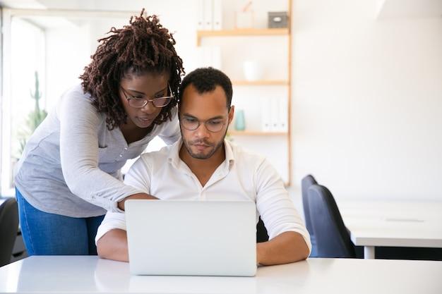 Profesional ayudando a nuevo empleado con informe