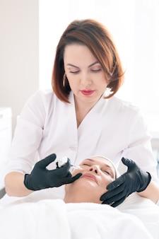 Profesional de belleza en guantes quirúrgicos con jeringa mientras reduce los pliegues nasolabiales de la mujer madura con relleno