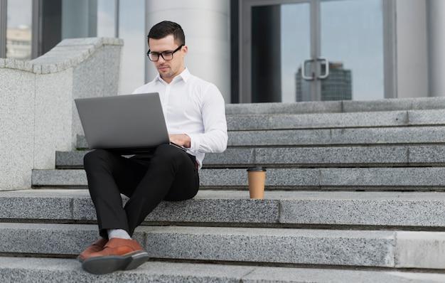 Profesional buscando en la computadora portátil al aire libre