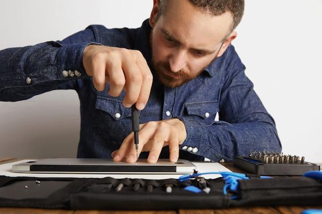 Profesional desenroscando con precisión la carcasa de la computadora portátil delgada metálica en su laboratorio de servicio eléctrico cerca de la bolsa de herramientas para limpiarla y repararla, vista frontal