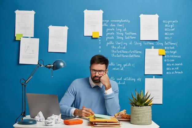 El profesional masculino cansado infeliz escribe en el bloc de notas, tiene expresión enojada, no tiene ideas creativas para hacer un proyecto