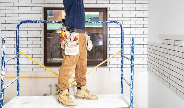 Profesional en monos con herramientas en el sitio de reparación.