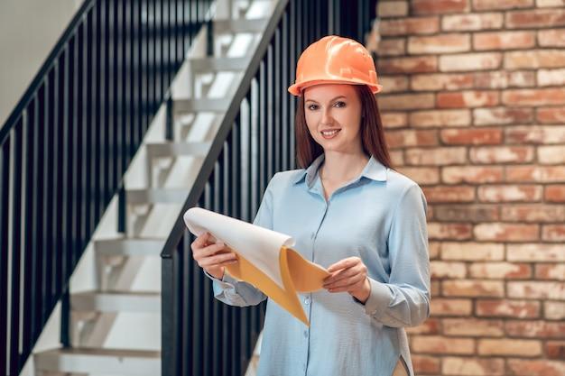 Profesional. mujer adulta joven sonriente en casco de seguridad de construcción de pie con plan de construcción cerca de escaleras en el interior