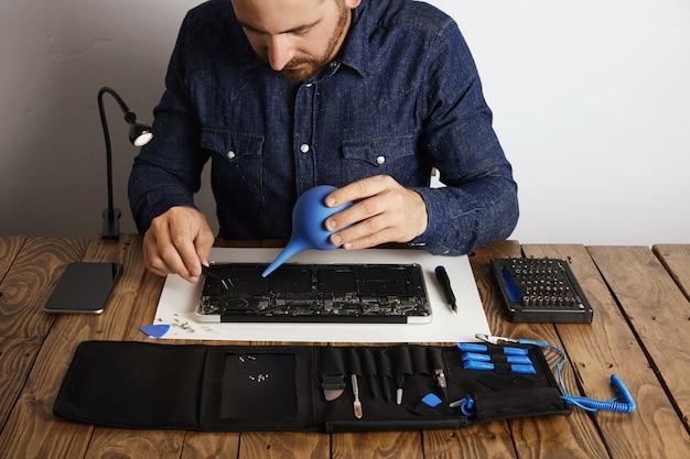 El profesional está trabajando en su laboratorio para reparar y limpiar la caja del kit de herramientas de la computadora portátil con instrumentos específicos cerca