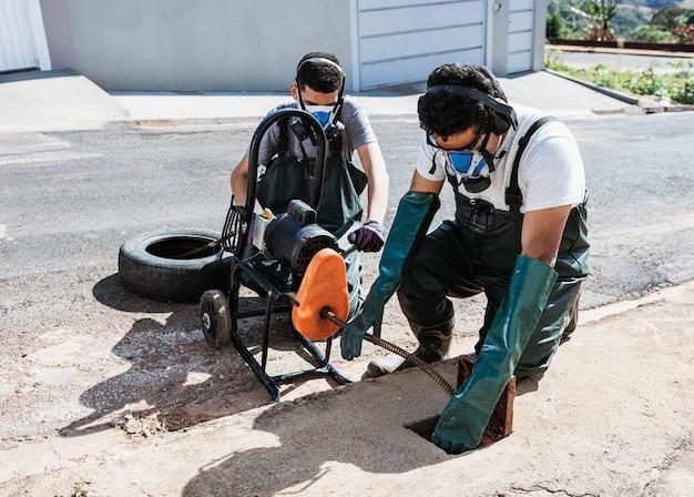Profesionales desbloqueando alcantarillas en la acera de la calle. desatascar eléctrico