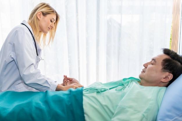 Profesionales de la medicina caucásica tomar el pulso con paciente hombre en la habitación del hospital.