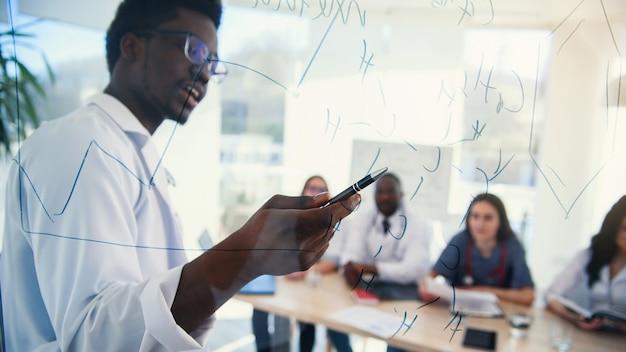 Profesor africano en conferencia médica en clínica moderna enseña a sus alumnos. doctor escribiendo a bordo algunas fórmulas para pasantes en la sala de conferencias del hospital al amanecer.