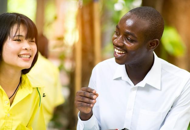 Profesor africano enseñando a estudiantes asiáticos sobre lenguas extranjeras con alegría.