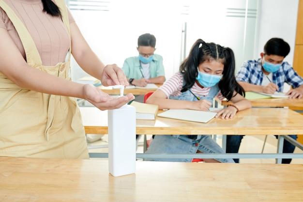 Profesor aplicando gel desinfectante en las manos cuando los estudiantes con máscaras médicas se sientan en escritorios y escriben en cuadernos