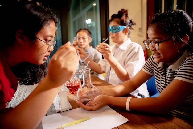 Profesor asiático y estudiante en la sala de laboratorio de ciencias de la escuela