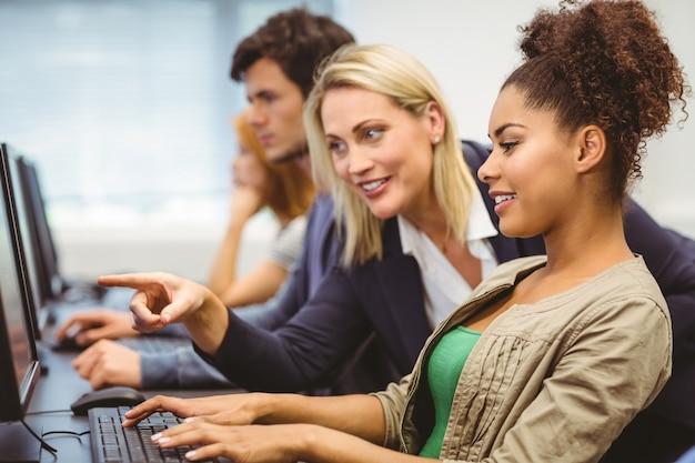 Profesor atractivo hablando con su estudiante en clase de informática