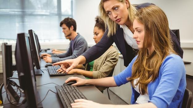 Profesor atractivo que ayuda a su estudiante en clase de informática