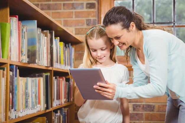 Profesor ayudando a un alumno a usar una tableta