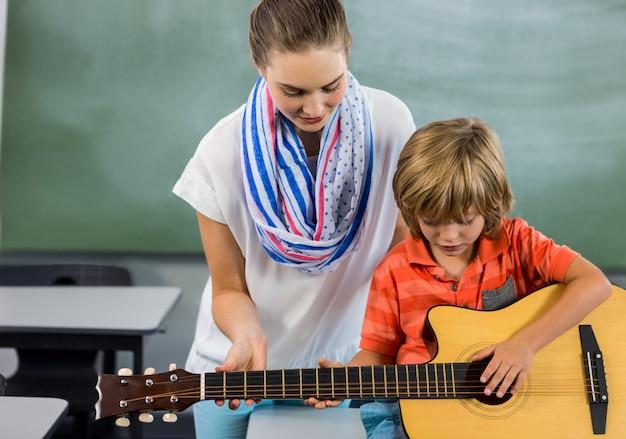 Profesor ayudando a boyto a tocar la guitarra en el aula