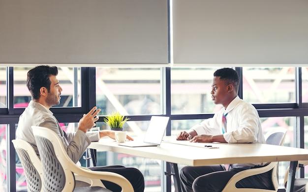 Profesor ayudando a hombre negro que trabaja en la computadora de la tableta en la escuela.