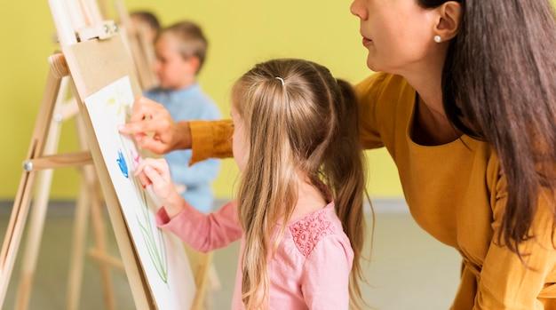 Profesor ayudando a niña en clase de dibujo
