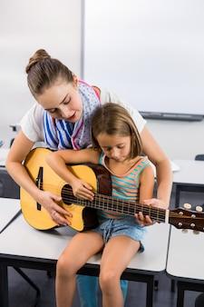 Profesor ayudando a niña a tocar la guitarra en el aula