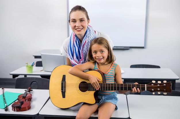 Profesor ayudando a niña a tocar la guitarra