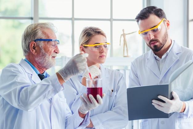 Profesor de ciencias y equipo de estudiantes trabajando con químicos en laboratorio.