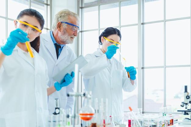 Profesor de ciencias y equipo de estudiantes trabajando con químicos en el laboratorio.