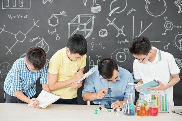 Profesor de ciencias mirando a través del microscopio a las bacterias en la placa de petri cuando los estudiantes de la escuela de pie cerca y escribiendo en libros de texto