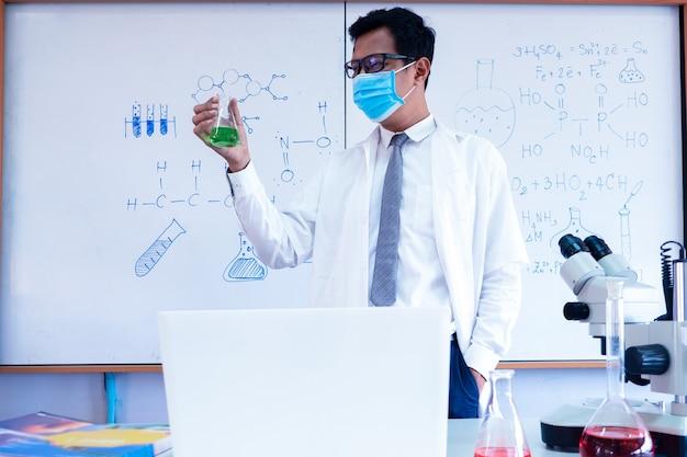 Profesor de ciencias químicas con máscara y enseñando en el aula