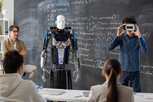 Profesor y compañeros de clase adolescentes mirando a uno de los estudiantes con auriculares vr haciendo presentación de robot contra la pizarra en la lección