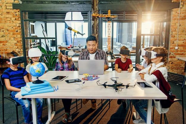 Profesor coreano con seis alumnos caucásicos que usan gafas de realidad virtual vr en un aula de informática de primaria.