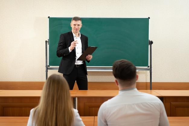 Profesor dando una conferencia en un aula y escribiendo fórmulas matemáticas en el tablero