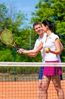 Profesor de deporte de tenis enseñando a mujer a jugar
