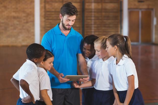 Profesor de deportes y niños de escuela usando tableta digital en cancha de baloncesto