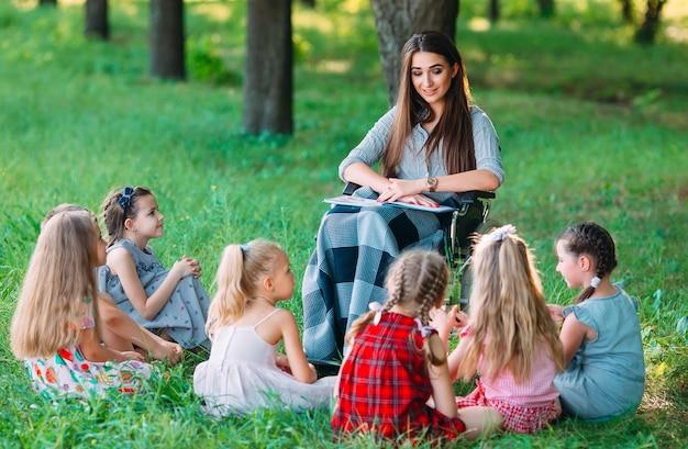 Profesor discapacitado conduce una lección con niños en la naturaleza.