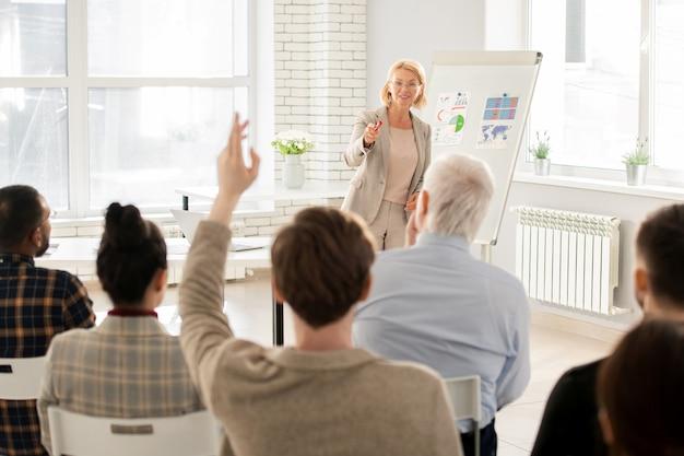 Profesor elegante apuntando a uno de los estudiantes en la lección después de hacer una pregunta sobre la conferencia