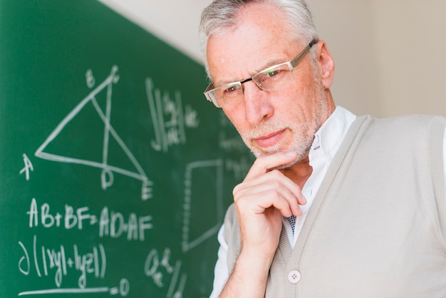 Profesor envejecido de pie cerca de la pizarra en el aula