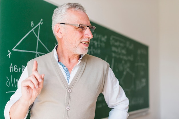 Profesor envejecido que da una conferencia cerca de la pizarra en sala de clase