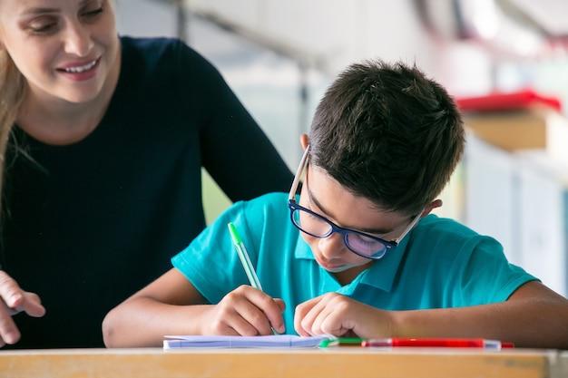 Profesor de escuela feliz viendo colegial en gafas haciendo tareas en clase