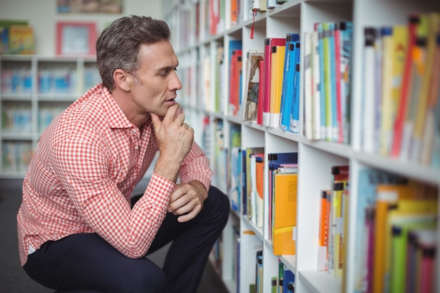 Profesor de escuela reflexivo seleccionando libro en biblioteca