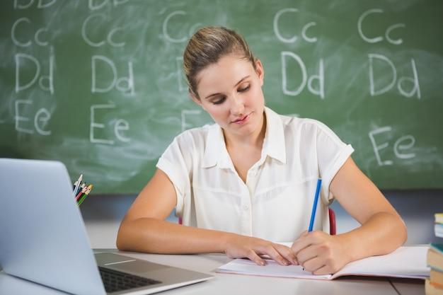 Profesor de la escuela revisando el libro en el aula