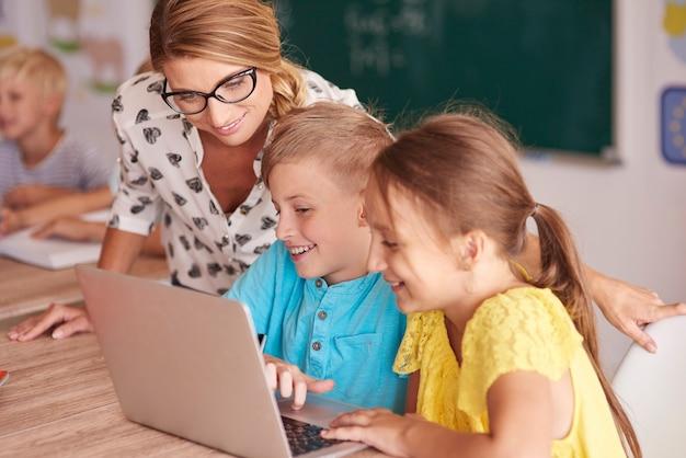 Profesor con estudiantes usando laptop en aula