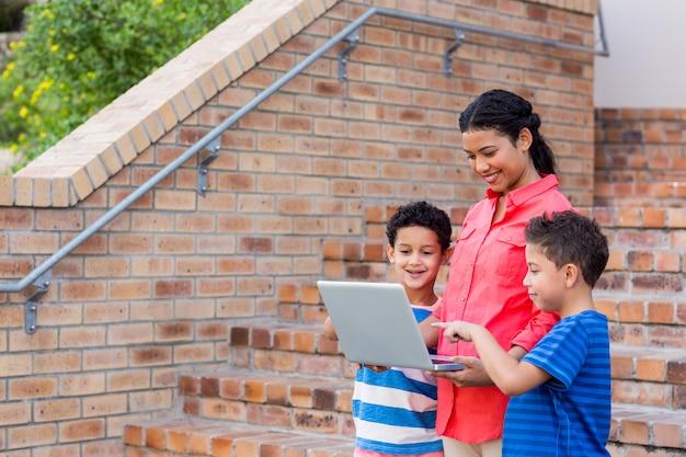Profesor con estudiantes usando laptop por pasos
