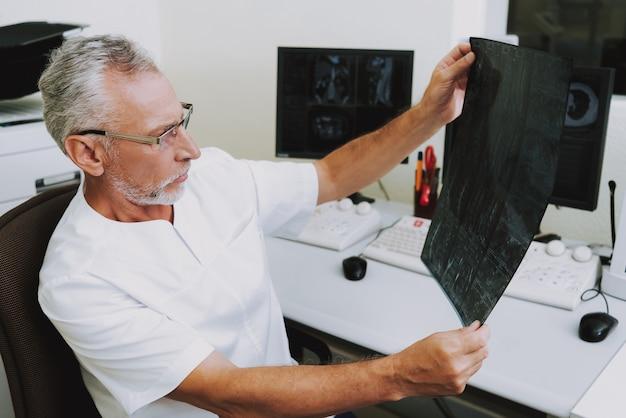 Profesor examinando radiografía en clínica de radiología